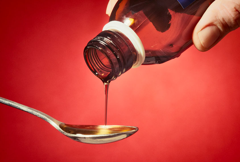 Liquid medicine being poured from bottle onto spoon.