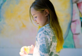 young autistic girl in playroom with a tennis ball that matches her yellow dyed hair.