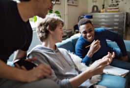 Smiling teenage boy showing mobile phone to friends on sofa while studying at home