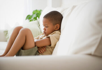 Young boy looking upset, sits on couch with crossed arms.