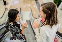 Two teen girls talking on an escalator.