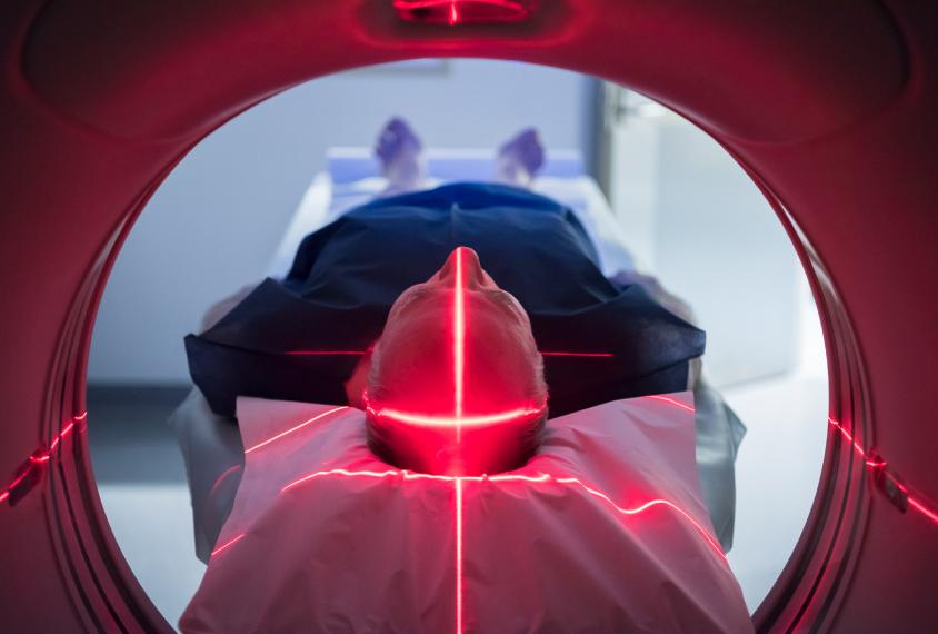 Senior man lying down in scanning machine.