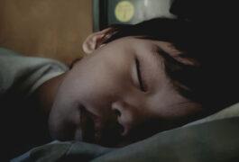 Boy sleeping in low light
