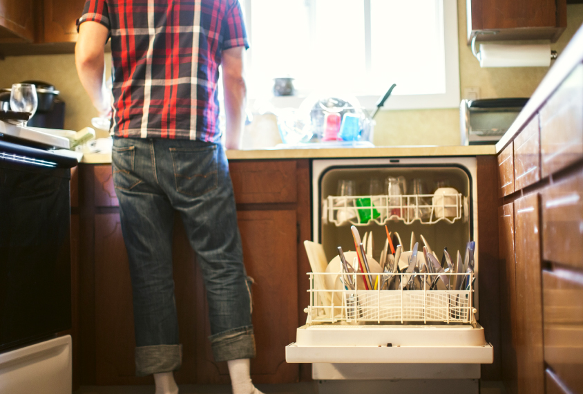 Young man at the kitchen sink next to open dishwasher.