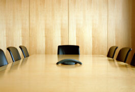 an empty conference room paneled in light colored wood, with 7 empty chairs and a conference phone.