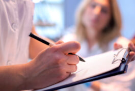 Doctor or clinician makes notes about patient during diagnosis.