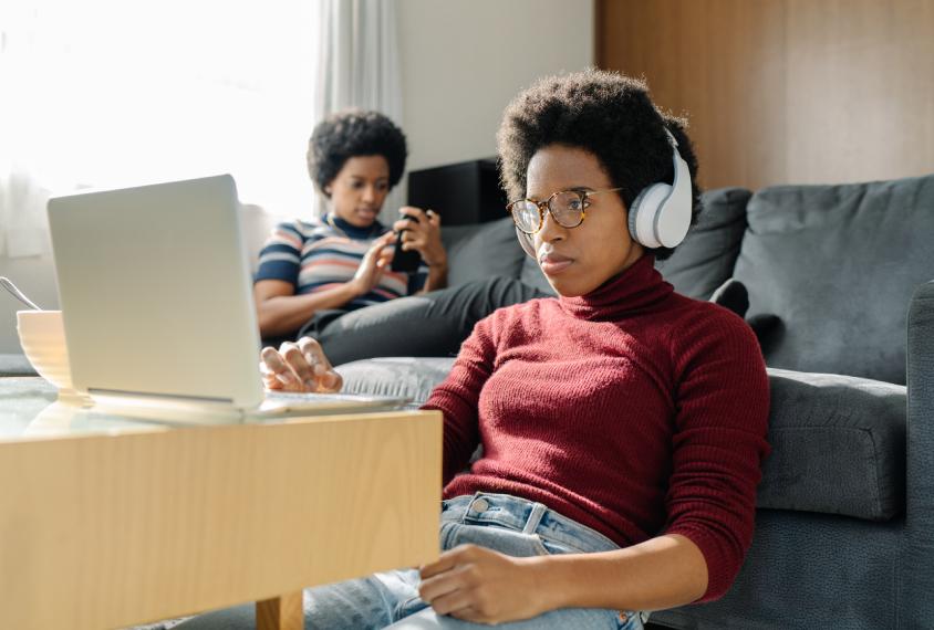 双胞胎姐妹在家使用笔记本电脑和智能手机度过他们的时间