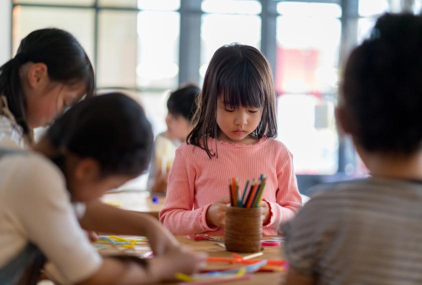 年轻女孩在幼儿园教室,集中。