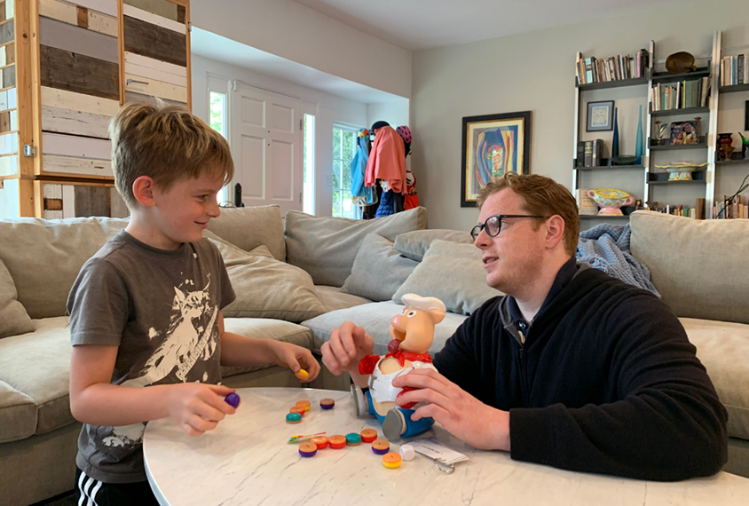 boy and his father with learning toys in living room.