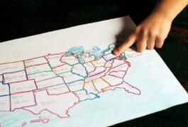 孩子的手指向美国在美国不同的蜡笔颜色的手绘地图上的位置。