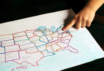 A child's hand points to a location on a hand drawn map of the United States in different crayon colors.