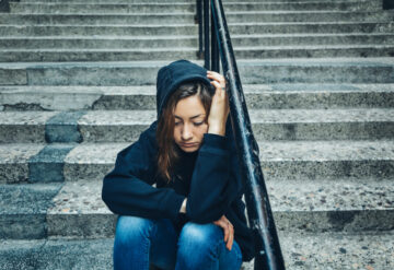 young woman sitting on steps alone, looking anxious.