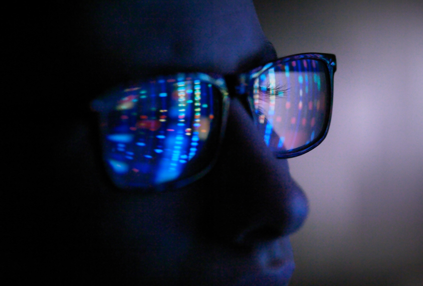 Computer screen reflection in spectacles of DNA profile, close up of face