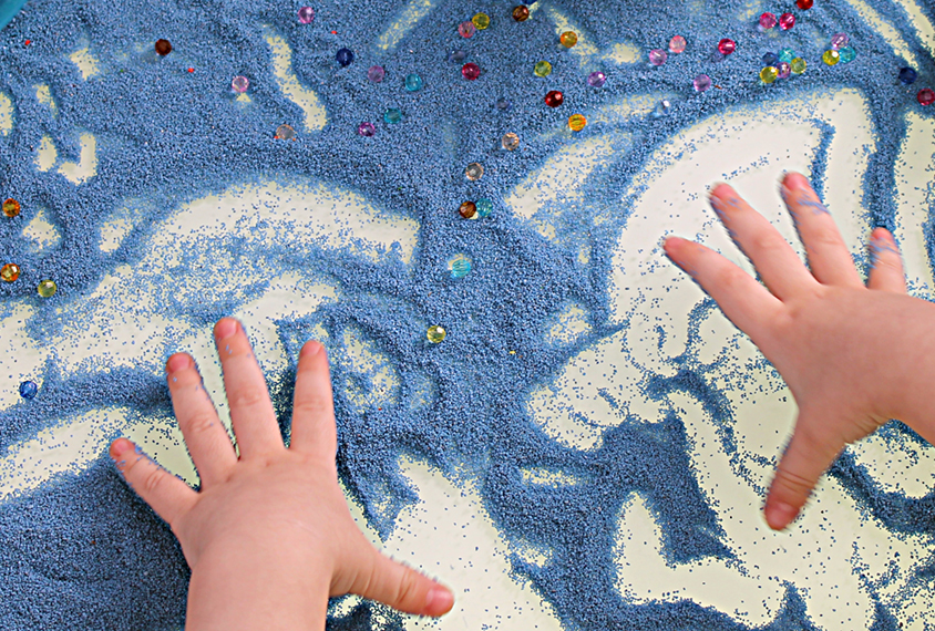 Child's hands playing on a white table with blue sand.