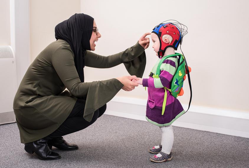 Woman talks to child in EEG cap