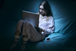 Teen girl up at night, looking at her computer.
