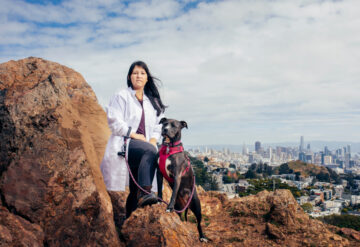 Portrait of Dr. Georgia Panagiotakos on a hill in San Francisco, with a view of the city behind her and her pet dog.