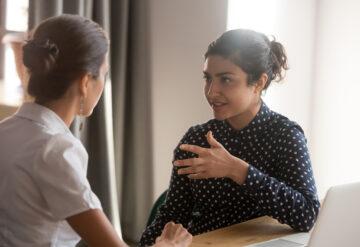 两个女人在交谈时眼神接触。