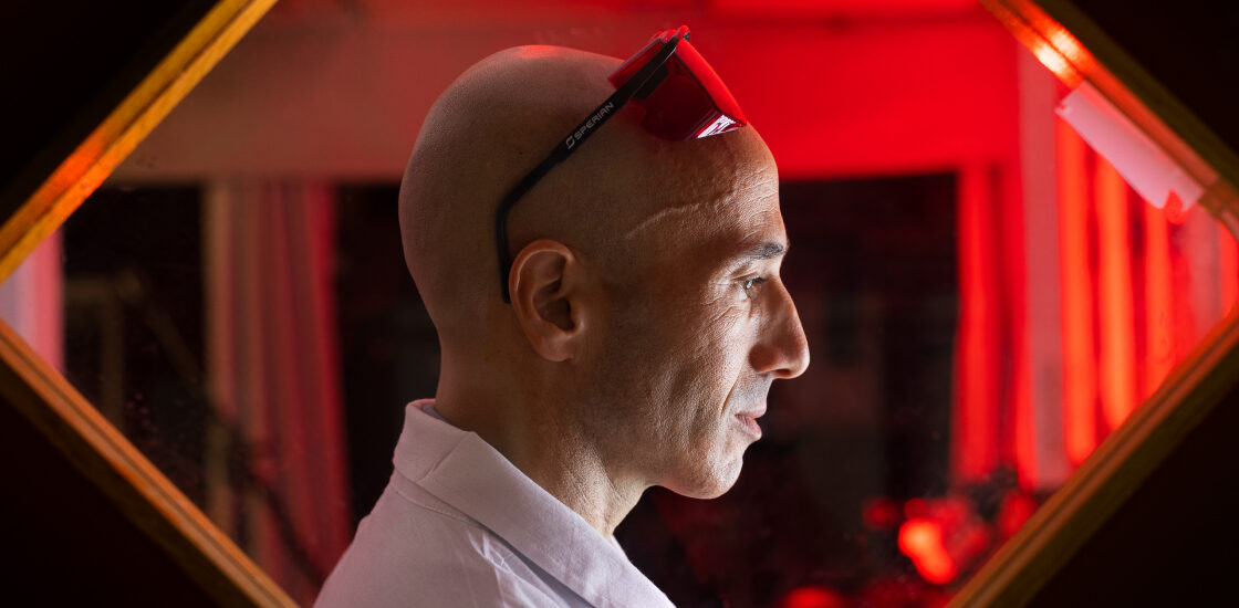 Ofer Yizhar in his lab, framed by rectangular window and a red background.