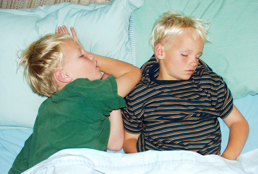 Twin boys sleeping on green sheets.