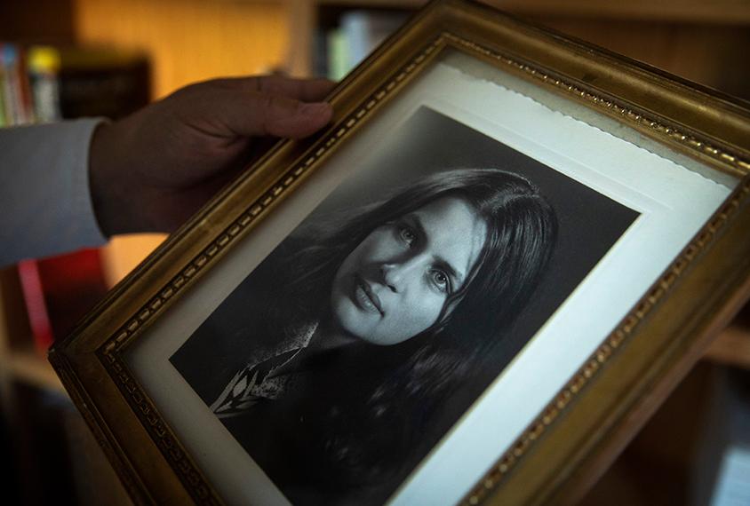 Eric Fombonne holds a framed portrait of his deceased sister.