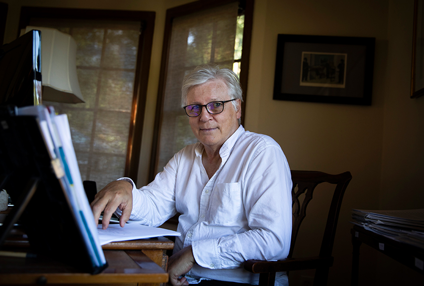 Portrait of Dr. Eric Fombonne working at his desk at home.