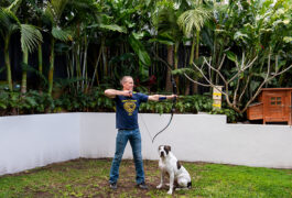 Scientist Ethan Scott takes aim with a bow and arrow in his backyard.