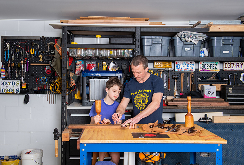 Scientist Ethan Scott in wood shop with his young son.
