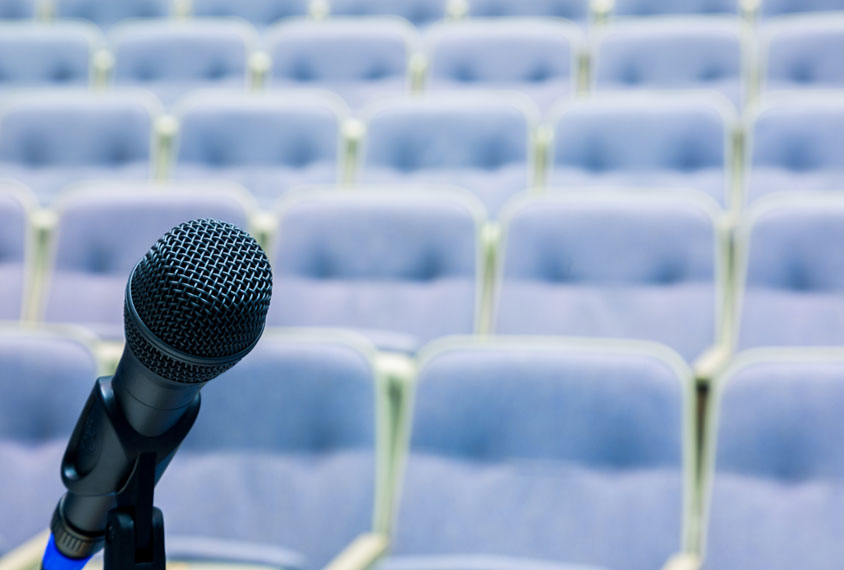 Empty conference room with closeup of microphone in foreground.