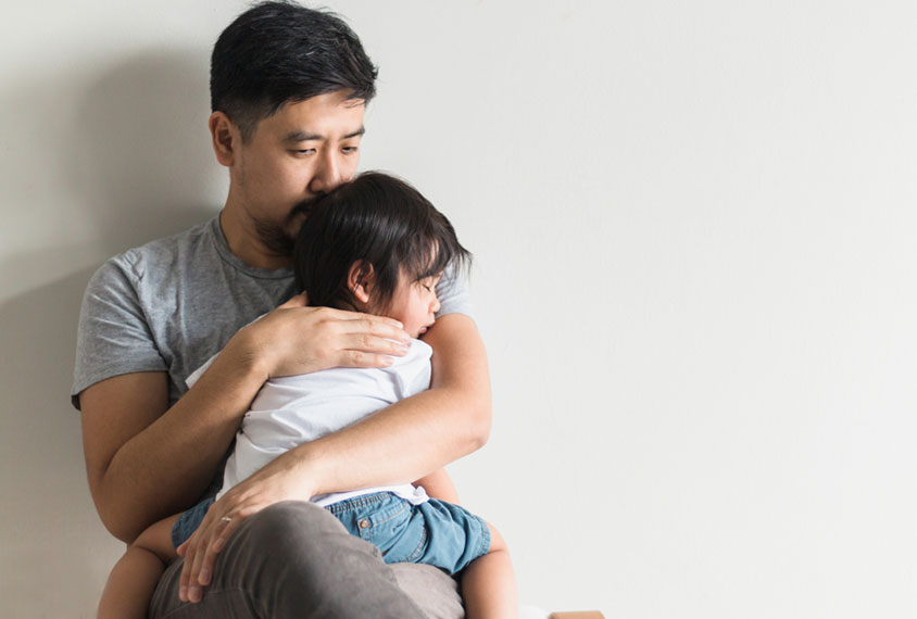 A concerned man holds his toddler close