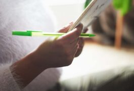 Person with documents and a green pen.