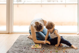 Mother and child playing with small colored blocks on the carpet.