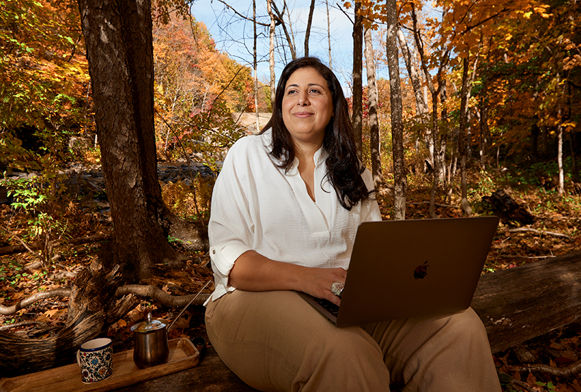 Mayada Elsabbagh with her laptop and coffee, in the woods near her home.