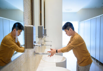 Photo: A boy in a yellow long-sleeve shirt washes his hands in a public restroom.